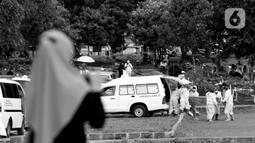 Anggota keluarga menyaksikan dari kejauhan proses pemakaman jenazah dengan protokol COVID-19 di TPU Bambu Apus, Jakarta, Kamis (28/1/2021). TPU Bambu Apus merupakan satu dari enam lokasi pemakaman jenazah dengan protokol COVID-19 yang disediakan Pemprov DKI Jakarta. (Liputan6.com/Helmi Fithriansyah)