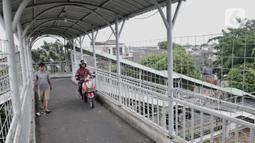 Warga dan pengendara motor melintasi jembatan penyeberangan orang (JPO) Stasiun Pasar Minggu Baru, Jakarta, Selasa (10/3/2020). JPO tersebut kerap disalahgunakan pengendara motor sebagai jalan alternatif untuk mempersingkat jarak tempuh meski rambu larangan sudah dipasang. (merdeka.com/Iqbal Nugroho