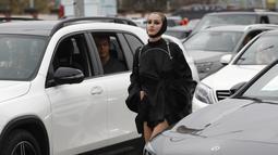 Seorang model berjalan melewati mobil saat drive-in fashion show bagian dari Praha Fashion Week di Praha, Republik Ceko, Sabtu (1/5/2021). Karena pembatasan virus corona, penonton hanya dapat melihat pertunjukan dari dalam mobil mereka. (AP Photo/Petr David Josek)