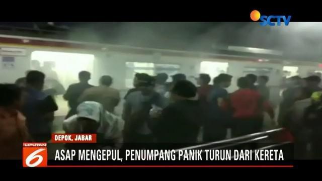 Asap cukup tebal mengepul di KRL jurusan Bogor saat berada di Stasiun Depok, Rabu (5/12) malam. Penumpang yang panik segera berhamburan keluar.