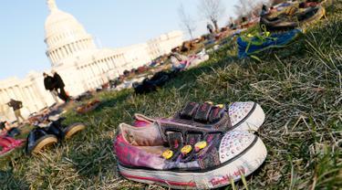 Ribuan sepatu menutupi halaman rumput di depan Gedung Capitol, Washington DC, Selasa (13/3). Sekitar 7000 ribu pasang sepatu dengan berbagai model diletakkan dan disusun secara trapesium. (Paul Morigi/AP Images for AVAAZ)