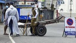 Aparat kepolisian memeriksa seorang warga yang tetap beraktivitas di luar rumah selama penerapan lockdown di Kolombo, Sri Lanka, Sabtu (21/8/2021). Rata-rata kasus harian Covid-19 di Sri Lanka kini mencapai 4.792 orang, melonjak lebih dari dua kali lipat dalam sebulan terakhir. (AFP/Ishara S. Kodika