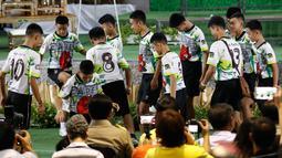 12 anak laki-laki dan pelatih sepak bola mereka, yang diselamatkan dari gua banjir di Thailand, memasuki ruang konferensi pers sambil menendang bola di Chiang Rai, Rabu (18/7). Mereka muncul di depan umum untuk pertama kalinya (AP/Vincent Thian)