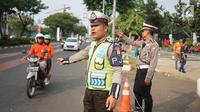 Petugas kepolisian mengatur arus lalu lintas kendaraan di sekitar SUGBK Senayan, Jakarta, Rabu (10/7/2019). Banyaknya kendaraan suporter Persija yang ingin menonton pertandingan membuat sejumlah arus lalu lintas dialihkan untuk mengurai kemacetan. (Liputan6.com/Immanuel Antonius)