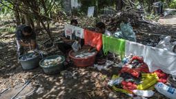 Aktivis Ecological Observation and Wetland Conservation (Ecoton) mencuci sampah plastik untuk membuat instalasi di Gresik, Jawa Timur, 17 September 2021. Instalasi tersebut di antaranya terbuat dari 4.444 botol. (JUNI KRISWANTO/AFP)