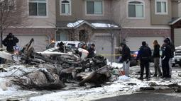Tim penyelamat melihat puing-puing pesawat pribadi yang jatuh di kawasan perumahan Roy, Utah, Amerika Serikat, Rabu (15/1/2020). Pesawat menabrak atap rumah sebelum akhirnya menghantam tanah dan terbakar. (Steve Griffin/The Deseret News via AP)