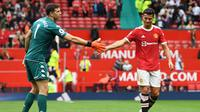 Kiper Aston Villa, Emiliano Martinez, menjabat tangan Cristiano Ronaldo setelah keberhasilan Villa meraih kemenangan atas Manchester United di Old Trafford, Sabtu (25/9/2021). (PAUL ELLIS / AFP)