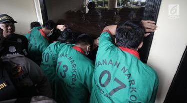 Sejumlah tersangka berbaris menghadap tembok saat ditampilkan dalam rilis pengungkapan 1,3 ton ganja di Polres Jakarta Barat, Kamis (4/1). Dalam kasus ini, petugas berhasil menyita 1,3 ton ganja  dengan enam orang tersangka. (Liputan6.com/Arya Manggala)