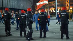 Seorang suporter Spartak Moskow berjalan melewati polisi di Stadion San Mames, Bilbao, Spanyol, Kamis (22/2). Polisi Inocencio Arias Garcia meninggal dunia karena mengalami serangan jantung saat bentrok. (ANDER GILLENEA/AFP)