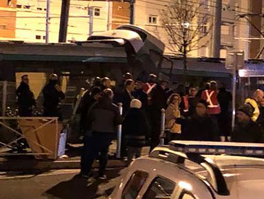 Personel layanan darurat berkumpul di lokasi tabrakan antara dua rangkaian trem di wilayah Issy-les-Moulineaux, Paris, Senin (11/2). Kecelakaan langka yang terjadi di pinggiran barat daya Paris itu mengakibatkan 12 orang terluka. (Philippe DUPEYRAT / AFP)