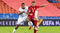 Pemain Jerman, Jonathan Tah, berebut bola dengan pemain Swiss, Haris Seferovic, pada laga UEFA Nations League di Stadion St. Jakob-Park, Senin, (7/9/2020). Kedua tim bermain imbang 1-1. (Georgios KefalasKeystone via AP)