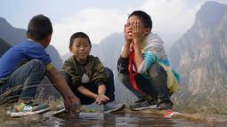 Sejumlah anak mencuci muka saat sampai di atas tebing Desa Atuleer, Tiongkok, Rabu (19/11). Sebelumnya, selama belasan tahun warga hanya menggunakan ranting pohon sebagai tangga untuk akses menuju kaki gunung. (REUTERS)