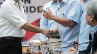 Tim kampanye Jokowi-Ma'ruf Amin, Aria Bima menyapa Ferry Mursidan Baldan dari Badan Pemenangan Nasional Prabowo-Sandi saat rapat koordinasi persiapan debat pasangan Capres dan Cawapres 2019 di Gedung KPU Jakarta, Rabu (19/12). (Liputan6.com/Faizal Fanani)