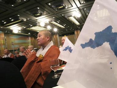 Seorang biksu wanita berdoa di samping bendera unifikasi selama Konferensi Perdamaian Bhikkhuni Buddha Dunia di Seoul, Korea Selatan (12/4). Mereka melakukan doa untuk persatuan Korea Utara dan Korea Selatan. (AP Photo / Ahn Young-joon)
