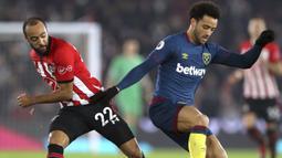 Pemain West Ham United, Felipe Anderson, berebut bola dengan pemain Southampton, Nathan Redmond, pada laga Premier League di Stadion St Mary, Kamis (27/12). West Ham United menang 2-1 atas Southampton. (AP/Andrew Matthews)