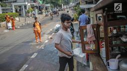 Pedagang menggunakan odol diwajah menghindari sisa gas air mata pasca bentrok massa dengan aparat di Palmerah, Jakarta, Kamis (26/9/2019). Banyak masyarakat yang melintas dan warga sekitar perih pada mata hingga bersin akibat sisa gas air mata pasca bentrokan kemarin. (Liputan6.com/Faizal Fanani)