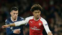 Pemain Arsenal, Reiss Nelson berebut bola dengan pemain Red Star Belgrade, Nemanja Radonjic pada penyisihan Grup H Liga Europa di Emirates Stadium, Jumat (3/11). The Gunners ditahan imbang tanpa gol oleh tim tamu. (AP /Tim Ireland)