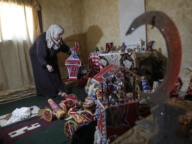 """Hanan al-Madhoun (37) membuat lentera tradisional yang disebut """"fanous"""" di rumahnya di Kota Gaza, menjelang bulan suci Ramadan dan di tengah pandemi virus corona, pada 1 April 2021. Warga biasanya memasang lentara sebagai dekorasi rumah untuk merayakan dimulainya Ramadan. (MAHMUD HAMS / AFP)"""