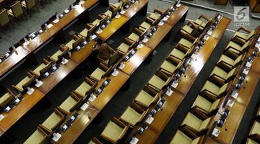 Seorang anggota DPR menghadiri rapat paripurna Masa Sidang I Periode 2019-2020 di antara bangku yang tak terisi di Kompleks Parlemen, Senayan, Jakarta, Kamis (22/8/2019). Rapat yang membahas RUU APBN Tahun 2020 beserta nota keuangannya itu hanya dihadiri 55 orang. (Liputan6.com/Johan Tallo)