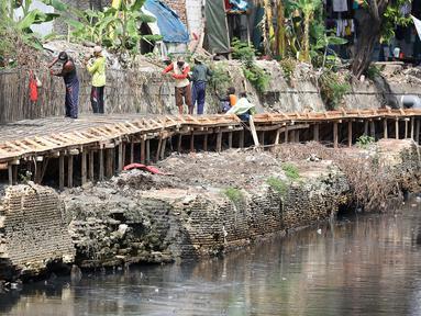 Pekerja mengerjakan proyek pembangunan tanggul bantaran Kali Anak Ciliwung di RT 001 RW 008 Ancol, Pademangan, Jakarta Utara, Kamis (19/12/2019). Pembangunan tanggul untuk mencegah amblesnya bantaran sungai seperti pada akhir tahun 2018 lalu. (Liputan6.com/Johan Tallo)