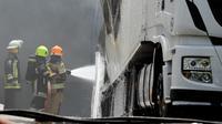 Petugas memadamkan sebuah truk yang terbakar akibat tertimpa pesawat kecil yang jatuh dekat pasar swalayan daerah permukiman di Tires, Portugal, Senin (17/4). Akibat insiden tersebut, beberapa mobil lain dan rumah disekitarnya terbakar. (andre nobre/AFP)