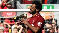 Penyerang Liverpool, Mohamed Salah, mengankat trofi Sepatu Emas Premier League usai laga melawan Brighton & Hove Albion di Stadion Anfield, Minggu (13/5/2018). Salah menjadi top scorer Premier League musim ini dengan raihan 32 gol. (AFP/Paul Ellis)