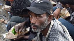 Sejumlah warga Rohingyah menikmati makanan di sbuah pos Lanal Kuala Idi, Aceh Timur (4/12). Menurut pihak berwenang, para pengungsi Rohingya mendarat ke perairan Idi dengan menggunakan perahu tepat pukul 08.00 WIB. (AFP Photo/Cek Mad)