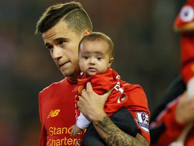 Gelandang Liverpool Philippe Coutinho menggendong putrinya saat salam penghormatan usai berakhirnya pertandingan melawan Chelsea pada pertandingan Liga Inggris di Anfield, Liverpool, 12 Mei 2016. (Reuters / Andrew Yates)