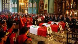 Keluarga dan rekan kerja mengahadiri upacara pemakaman di sebuah gereja di Lima, Peru (21/10). Tiga petugas pemadam kebakaran tewas saat bertugas memadamkan api di sebuah pabrik sepatu di Kota Lima. (Reuters/Guadalupe Pardo)