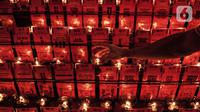 Warga keturunan Tionghoa menyalakan lilin saat sembahyang malam Tahun Baru Imlek 2572 di klenteng kawasan Petak Sembilan, Glodok, Jakarta, Kamis (11/2/2021). Pembatasan waktu sembahyang malam Imlek kali ini sebagai langkah mencegah penyebaran COVID-19. (merdeka.com/Iqbal S. Nugroho)
