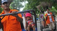 Seorang petugas kebersihan Jakarta membawa serta anaknya menarik gerobak untuk membersihkan sampah di Jakarta, Senin (14/4). (ANTARA FOTO/Zabur Karuru)