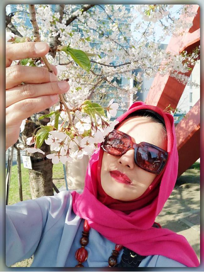 """Terharuuuu... mau nangis rasanya menyentuh Sakura putih ini,"" tulis marissahaque yang pandangannya tertuju pada bunga sambil memegang tangkainya pada bunga yang jarang mekar tersebut. (Instagram/marissahaque)"