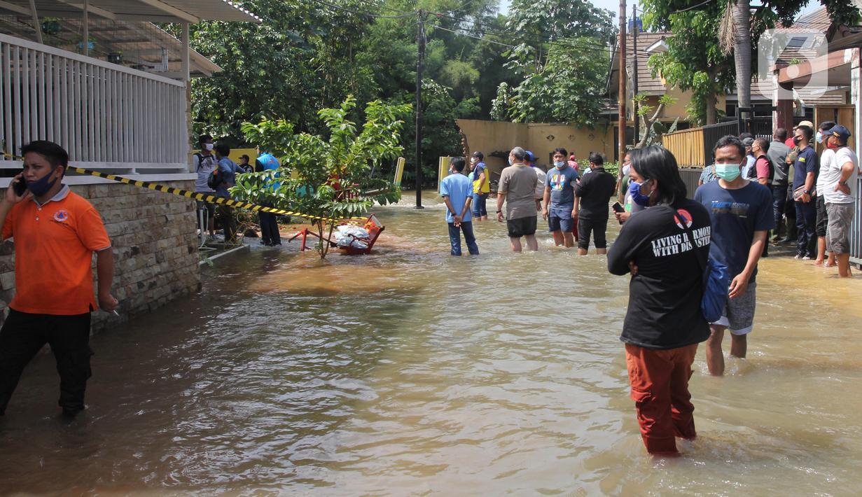 Warga memantau banjir akibat jebolnya tanggul karena tertimpa tanah longsor, di Perumahan Nerada Estate Ciputat, Tangerang Selatan, Sabtu (12/6/2021). Longsor yang menimpa sejumlah rumah membuat tanggul pembatas kali jebol dan air meluap sehingga menyebabkan banjir. (Liputan6.com/Angga Yuniar)
