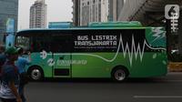 Warga memfoto bus Transjakarta bertenaga listrik saat karnaval kendaraan listrik di Jalan Jenderal Sudirman, Jakarta, Minggu (27/10/2019). Karnaval kendaraan listrik ini bertajuk, Jakarta Langit Biru. (Liputan6.com/Helmi Fithriansyah)