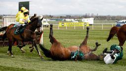 Kuda bernama Curious Carlos terjatuh saat ditunggai oleh Sean Bowen pada pacuan kuda festival nasional Crabbie Grand Liverpool, Inggris, (7/4/2016). Acara yang digelar setiap tahun ini selalu menjadi daya tarik warga Inggris. (Reuters / Andrew Boyers)