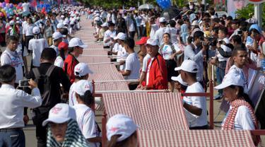 Warga Kamboja membentangkan syal krama sepanjang 1.149,8 meter untuk memecahkan rekor Guinness sebagai syal tenun terpanjang dunia di Phnom Penh, Minggu (1/7). Lebih dari 23.000 orang berpartisipasi membentangkan syal tersebut. (AFP/TANG CHHIN Sothy)