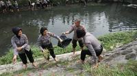 Sejumlah anggota Polwan Polresta Solo memperingati Hari Air Sedunia dengan membersihkan sampah di Sungai Gajah Putih Solo, Rabu (21/3).(Liputan6.com/Fajar Abrori)