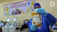 Petugas medis menunjukkan plasma konvalesen hasil donor dari penyintas COVID-19 di PMI DKI Jakarta, Selasa (19/1/2021). Sebanyak 307 penyintas COVID-19 per 1 hingga 15 Januari 2021 telah mendonorkan plasma konvalesen. (Liputan6.com/Herman Zakharia)