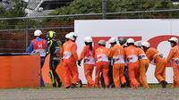 Para marshals membantu Valentino Rossi yang terjatuh pada lap ke-20 di MotoGP Jepang yang berlangsung di Sirkuit Twin Ring Motegi, Minggu (20/10/2019). (AFP/Toshifumi Kitamura)