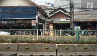 Kondisi pagar pembatas jalur transjakarta yang ditopang bambu di Jalan Otista Raya, Jakarta, Jumat (5/7/2019). Meskipun telah lama rusak, pagar besi berjeruji yang berfungsi sebagai pembatas agar orang tidak menyeberang secara sembarangan itu belum juga diperbaiki. (Liputan6.com/Immanuel Antonius)
