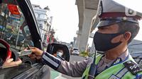 Polisi memeriksa surat kendaraan di kawasan Fatmawati, Jakarta, Senin (10/8/2020). Ditlantas Polda Metro Jaya kembali menerapkan sanksi tilang terhadap kendaraan roda empat yang melanggar peraturan ganjil genap di masa Pembatasan Sosial Berskala Besar (PSBB) transisi. (Liputan6.com/Herman Zakharia)