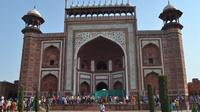 Orang-orang berkumpul di sekitar royal gate atau gerbang kerajaan setelah pilar Taj Mahal (kedua kanan) runtuh di Agra, India, Kamis (12/4). Kendati demikian, hingga berita ini diturunkan tidak ada korban jiwa dalam peristiwa tersebut. (AFP Photo)