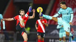 Pemain Southampton, Jack Stephens, berebut bola dengan penyerang Liverpool, Roberto Firmino, pada laga Liga Inggris di Stadion St Mary's, Selasa (05/01/2021). Liverpool takluk 1-0 dari Southampton. (AP Photo/Michael Steele,Pool)