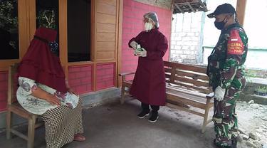 Babinsa dari Kodim 0721/Blora dengan didampingi tenaga medis mendistribusikan obat secara gratis untuk pasien Covid-19 dengan gejala ringan atau OTG yang menjalani isoman. (Liputan6.com/Ahmad Adirin)
