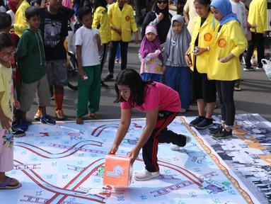 Mahasiswa jurusan Kriminologi Fisip UI mendampingi anak-anak bermain ular tangga saat gelaran Car Free Day di kawasan Bundaran HI, Jakarta, Minggu (18/11). Permainan ini bertujuan mengurangi anak-anak bermain gawai. (Liputan6.com/Helmi Fithriansyah)