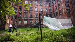 Sejumlah orang berjalan melewati salah satu bangunan asrama untuk para pekerja pabrik tekstil Proletarka di Kota Tver, Rusia, 8 Agustus 2020. Proletarka merupakan satu set barak unik yang terdiri dari sekitar 50 bangunan neo-Gotik. (Alexander NEMENOV/AFP)