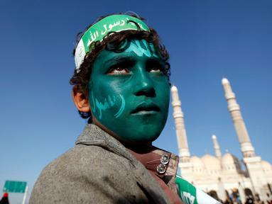 Seorang remaja dengan wajah yang dicat hijau dan bertuliskan kalam Allah, mengikuti peringatan hari kelahiran Nabi Muhammad di Sanaa, Yaman (11/12). (Reuters/Khaled Abdullah)