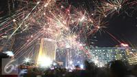 Kemeriahan kembang api menghiasi malam pergantian tahun di kawasan Bundaran HI, Jakarta, Sabtu (31/12). Ribuan warga di kawasan Bundaran HI, Jakarta riuh dan semarak menyambut tahun baru. (Liputan6.com/Immanuel Antonius)