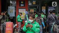 Sejumlah pengemudi ojek online berkerumun saat antre mengambil pesanan di gerai cepat saji McDonald's Raden Saleh, Jakarta, Rabu (9/6/2021). BTS Meal merupakan menu kolaborasi boyband asal Korea, BTS, dengan McDonald's yang hadir di 50 negara termasuk Indonesia. (Liputan6.com/Faizal Fanani)