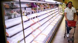 Seorang pembeli berjalan melewati rak kosong di sebuah toko di Tokyo, Jumat (11/10/2019). Banyak toko-toko perbelanjaan di Jepang yang kehabisan makanan dan minuman akibat warganya yang menimbun makanan untuk menghadapi topan Hagibis. (Franck FIFE / AFP)